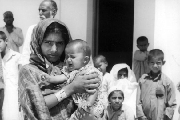 Photograph by Noor Ali Rashid, taken in the aftermath of the April 1968 shipwreck. As part of his coverage, Rashid recorded that the woman was Mrs. Sahil Maula Baksh of Sindh's Dadu district. She holds Alam Khatoon, whose parents did not survive. Source: Lasting Impressions: Noor Ali Rashid The Royal Photographer, Sharjah Art Museum.